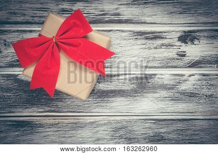 Holiday and birthday concept. Gift with red ribbon on a wooden board.