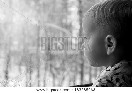 Little cute blond child looking out of the window. black and white photography