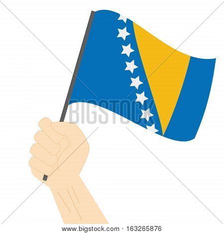Hand holding and raising the national flag of Bosnia and Herzegovina
