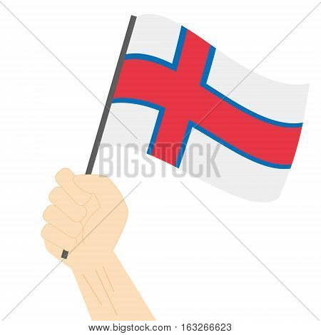 Hand holding and raising the national flag of Faroe Islands
