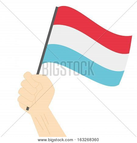 Hand holding and raising the national flag of Luxembourg