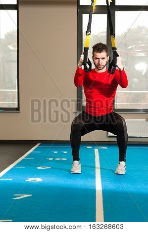 one white curly-haired, bearded sporty male exercising with fitness trx straps in the