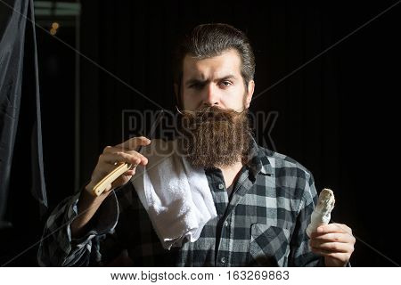 Handsome man bearded hipster brunette with long beard and moustache shaves with open vintage razor with blade and shaving brush on dark background
