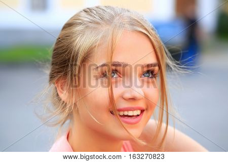 Pretty young woman or girl with tied in bun blonde hair in pink shirt with cute face smiling on sunny day