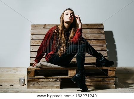 Pretty girl or beautiful woman cute sexy fashion model with long brunette hair in casual clothes sits on wooden pallet sofa on white wall