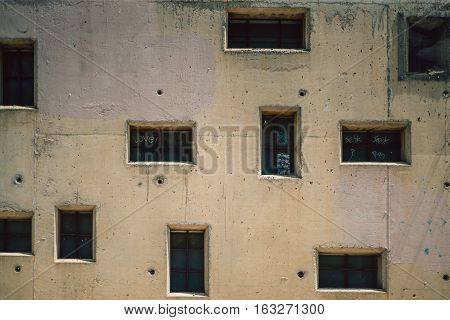 Close-up view of beige facade of residential house with irregular dark windows of different form and small circle holes sunny summer day Barcelona Spain