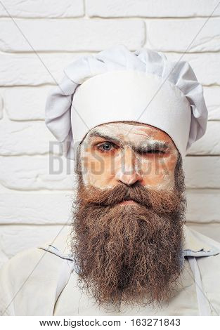 Handsome serious man cook or baker with flour on face beard and moustache poses in chef uniform and hat on white brick wall