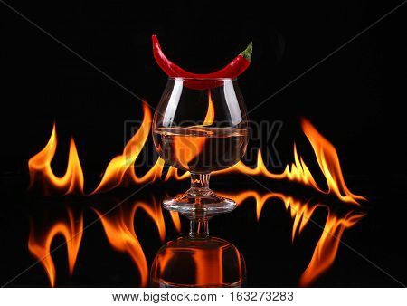 Hot Chili Pepper In A  Cognac Ballon With A Fire On A Black Background