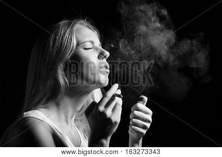 woman smoking joint of marijuana on black background, monochrome