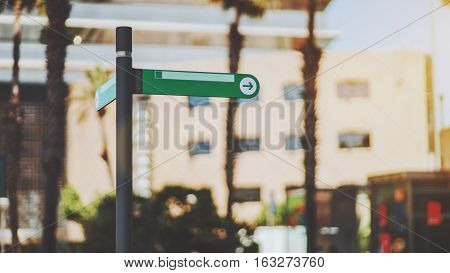 Narrow green waymark mock up with arrow inside of circle on street of summer city with blurred urban background with palms behind sunny day Barcelona Spain