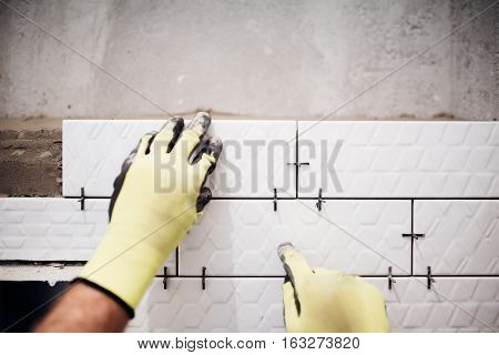 Professional Industrial Worker Installing Small Ceramic Tiles In Bathroom During Renovation Works