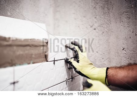 Industrial Worker Placing Small Ceramic Tiles With Plastic Spacer On Bathroom Walls