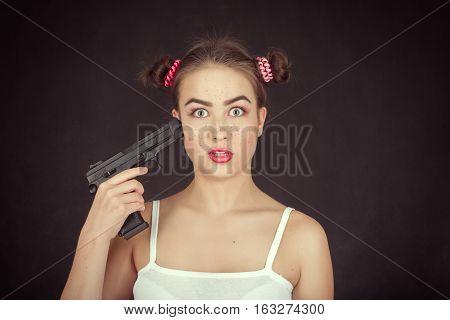 fun crazy girl teenager shooting herself on black background