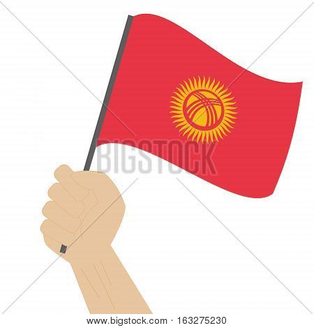 Hand holding and raising the national flag of Kyrgyzstan