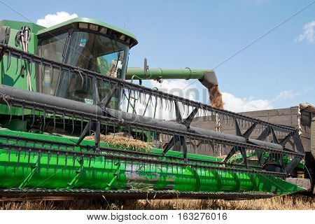 Kharkiv Ukraine - July 12 2011: Combine harvester load wheat in the truck at the time of harvest in a sunny summer day in Kharkiv Oblast Ukraine on July 12 2011