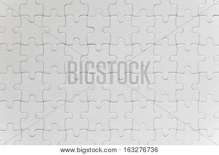 Blank white jigsaw puzzle pieces completed as copy space