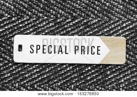 Clothes label lettered special price on tweed background