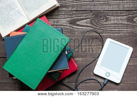 ebook and old books on wooden table. tablet download information from many books. new technology concept. top view
