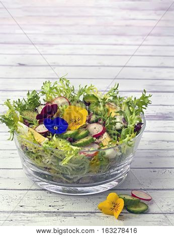 Bowl of organic salad decorated with edible pansy flowers on wooden background