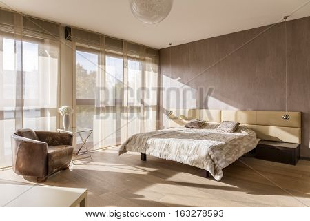 Spacious sunny bedroom interior with marital bed