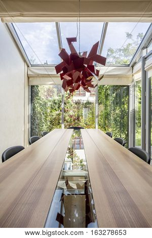 Dining area with wide wooden table and red chandelier
