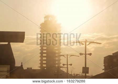The Skeletor: 92 metre high-rise building in Cracow, Poland. Sunrise in the city. Abandoned skyscraper