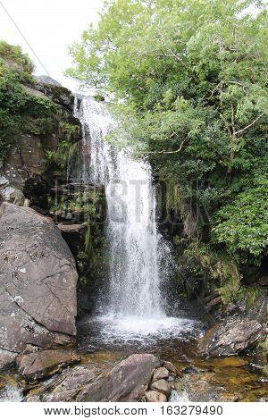 A High Waterfall Cascading Over a Hillside Rock Face.