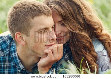 Beautiful loving couple lying on the field of dandelions