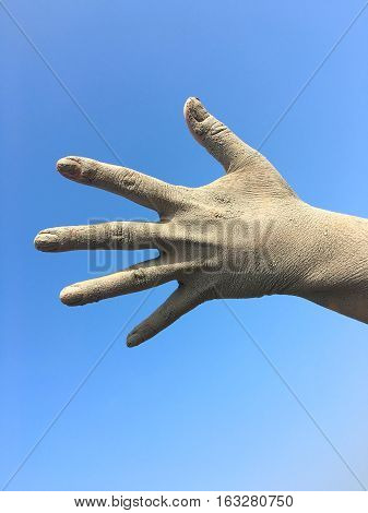 Women's human left hand in the splayed fingers of the hand in the dirt