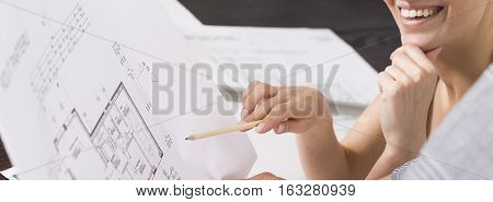 Smiling female architect analysing paper home floor plan
