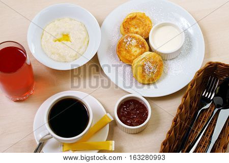 Table set for breakfast with rice porridge, cheesecakes with jam, berry drink, black coffee and cuttlery in wooden container in cafe