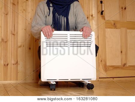 Woman froze and warms her hands on white electric convector heater with horizontal louvers in room of a new wooden house
