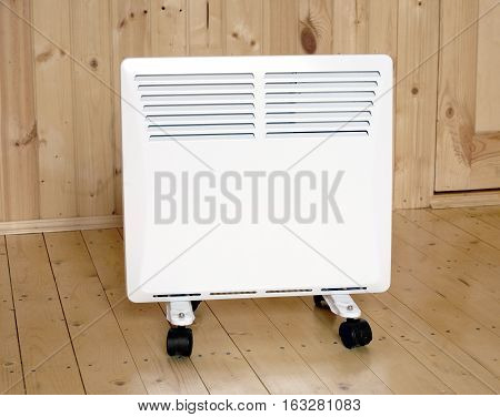 White electric convector heater with horizontal louvers in wooden house room