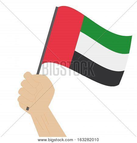 Hand holding and raising the national flag of United Arab Emirates UAE