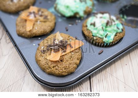 Homemade carrot muffins on a white wooden background. One big muffin with whipped cream and colorful and chocolate sprinkles