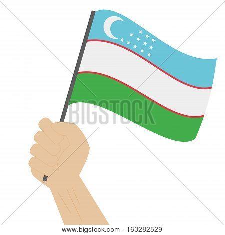 Hand holding and raising the national flag of Uzbekistan
