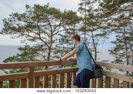 Man Sitting On The Wooden Stairs In Park And Smiling