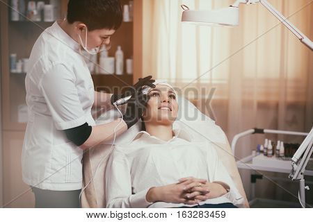 Cosmetologist applying permanent makeup on eyebrows - eyebrow tattoo. Permanent make-up tattoo at beauty salon. Permanent makeup. Aesthetic medicine, cosmetology. Cosmetology and makeup salon.