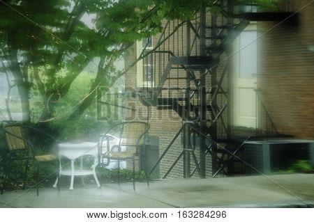 Rain blurs a summer sidewalk relaxation spot