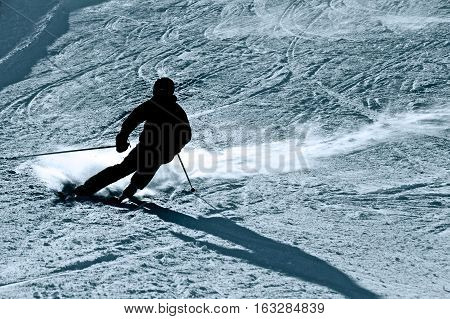 backlit silhouette of man in action practicing ski going fast and agressive down snow in winter sport concept and adventure vacation holidays