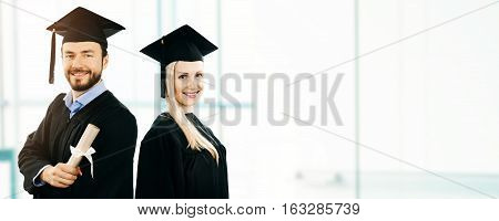 graduation - happy students wearing gown and cap. copy space