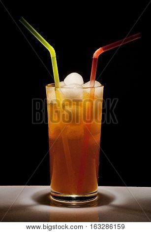 Tall glass with a drink and ice on black background