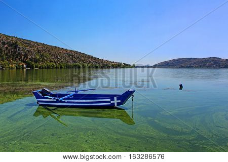 Blue traditional old wooden fishing boat in the lake Orestiada in Kastoria city of northern Greece