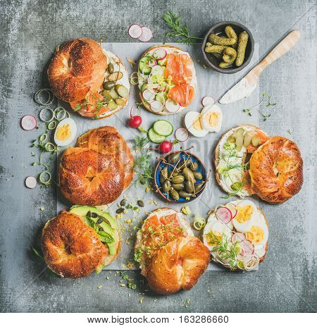 Variety of bagels with smoked salmon, eggs, radish, avocado, cucumber, greens and cream cheese for breakfast, healthy lunch or party over grey concrete background, top view. Takeaway food concept