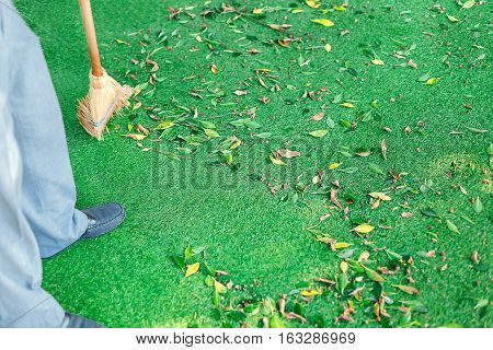 Working with a broom sweeps the lawn from the fallen leaves. The autumn season, working in the yard outdoors.