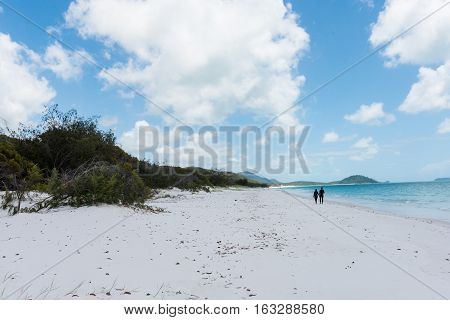 A couple walking on Whitehaven Beach, a 7 km stretch along Whitsunday Island in Queensland, Australia