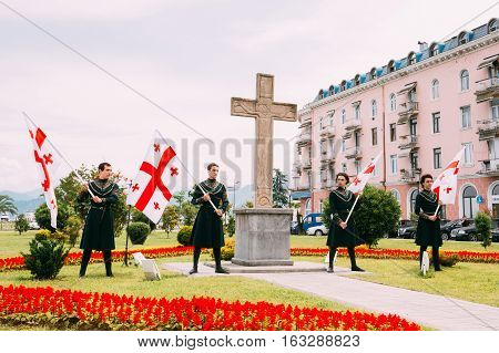 Batumi, Adjara, Georgia - May 26, 2016: Young men in Georgian national dress holding a national flags in celebration of the national holiday - the Independence Day of Georgia.