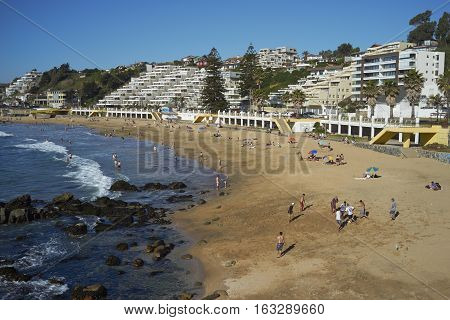 CONCON, CHILE - NOVEMBER 28, 2016: Sandy beach filled with people back by apartments and hotels at Concon on the Pacific Coast of Chile.