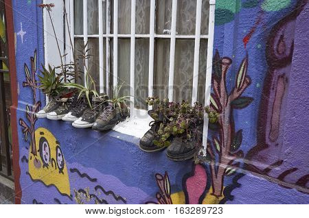 VALPARAISO, CHILE - NOVEMBER 29, 2016: Old shoes on a windowsill being used for plants in the historic coastal city of Valparaiso in Chile.