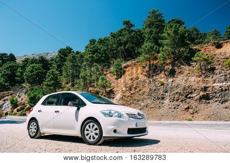 Mijas, Spain - June 19, 2015: White color Toyota Auris car on Spain nature landscape. The Toyota Auris is a compact hatchback derived from the Toyota Corolla